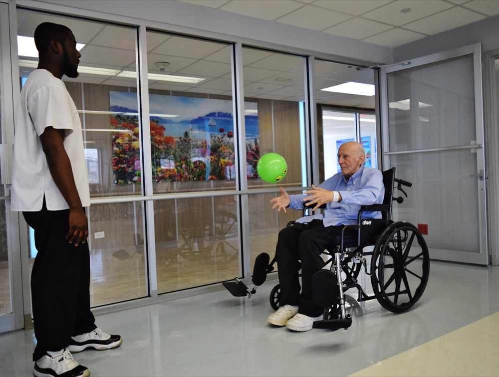 Man catching a therapy ball from therapist while sitting in wheelchair