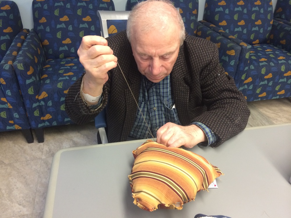 man sewing a cushion